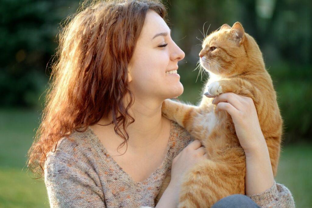 smiling woman holding ginger cat