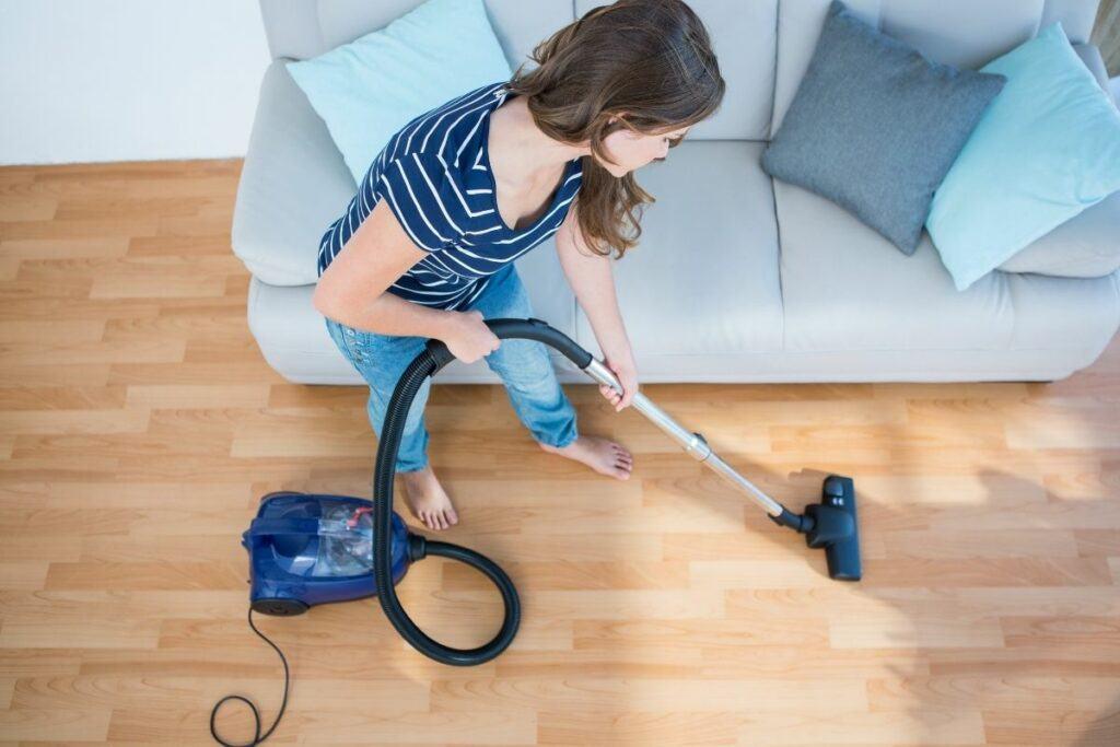 woman vacuuming wood flooring
